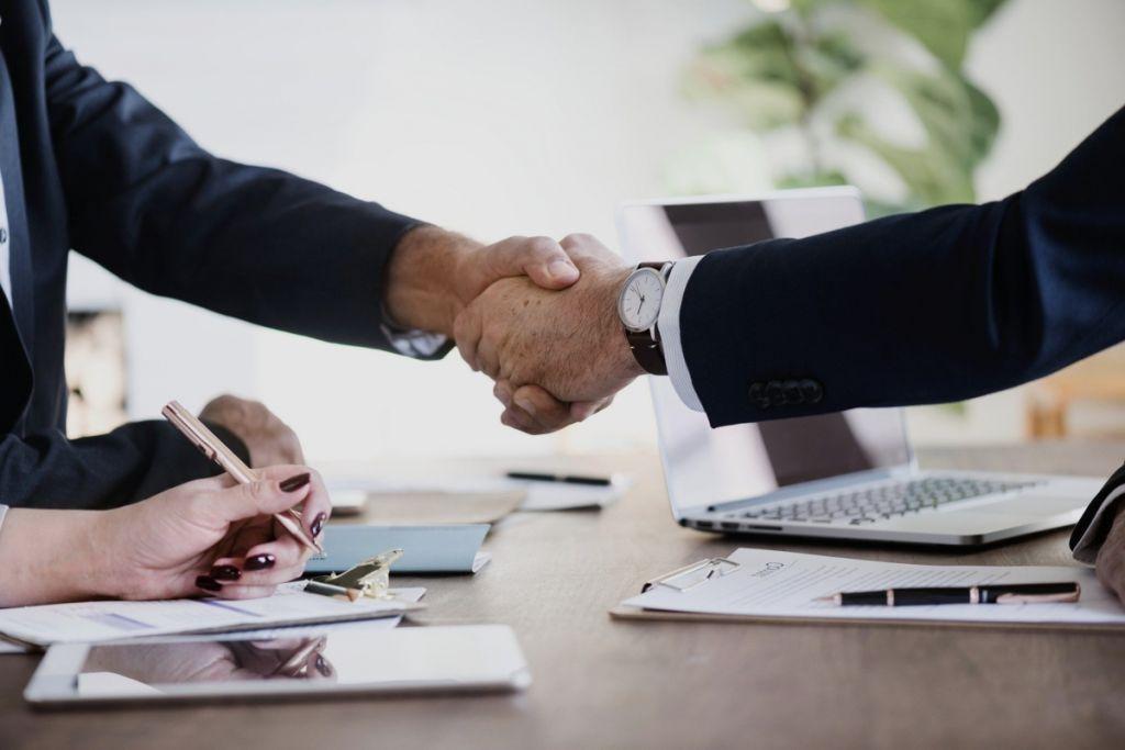 Dos personas firmando un contrato de un seguro de vida