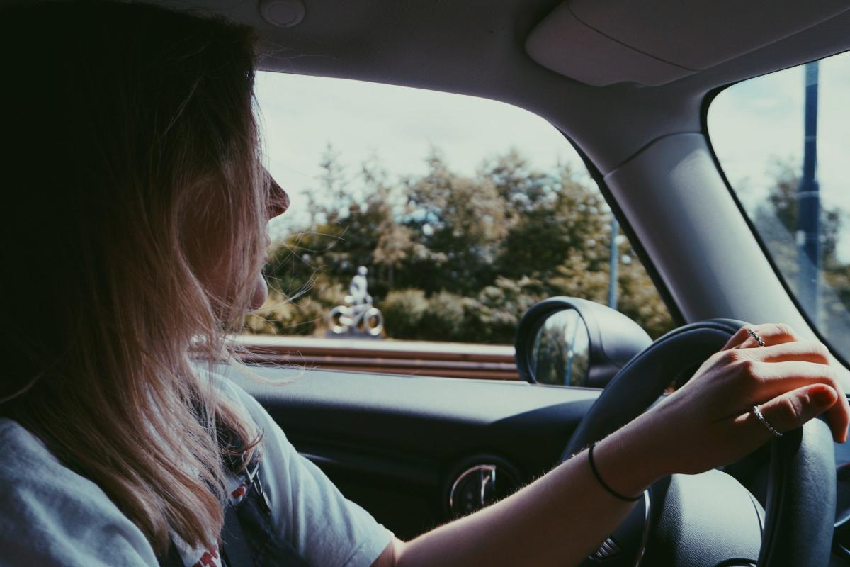 Mujer conduciendo tras haber devuelto el recibo del seguro del coche
